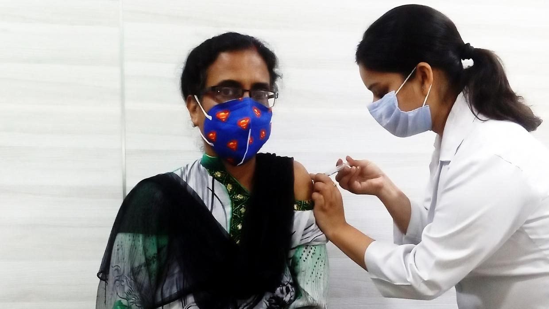 Eine Frau In Delhi erhält ihre erste Coronaschutzimpfung.