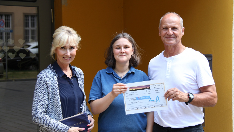 Pia (l.) und Thomas (r.) Grunenberg überreichen der Leiterin Anke Haase den Spendenscheck