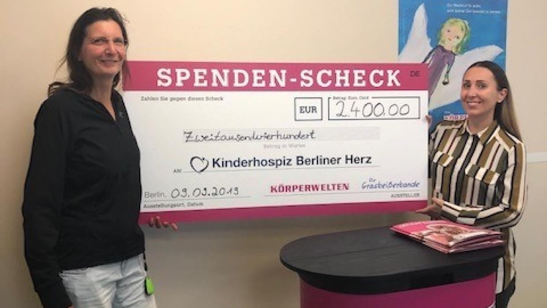 Beate Kachel von den KÖRPERWELTEN (r) übergibt den Spendenscheck an Kathi Bertolini, Pflegedienstleiterin des Kinderhospizes (l)