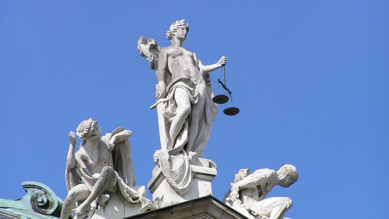 """Ausschnitt von Statuengruppe """"Gerechtigkeit"""" von Balthasar Schmitt, bestehend aus Justitia mit Waage und Schwert, sowie Unschuld (links) und Laster (rechts), auf dem Südgiebel des Justizpalastes in München   Foto: wikimedia commons (CC BY-SA 3.0)"""
